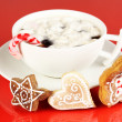 Cup of coffee with Christmas sweetness on red background — Photo