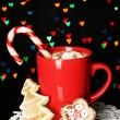 Cup of coffee with holiday candy on Christmas lights background — Stock Photo #19164235