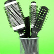 Iron basket with combs and round hair brushes, on color background - Stock Photo