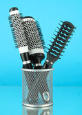 Iron basket with round hair brushes, on color background — Stock Photo