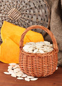 Pumpkin seeds in wicker basket, on wooden background — Stock Photo