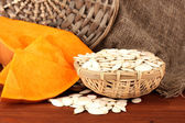 Pumpkin seeds in wicker box, on sackcloth background — Stock Photo