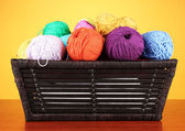Colorful yarn balls in basket on color background — Stock Photo