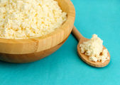 Cottage cheese in bowl on blue tablecloth — Stock Photo