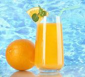 Glass of orange juice with mint and orange on sea background — Stockfoto