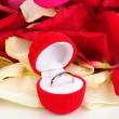 Beautiful box with ring on red, white and pink rose petals background isolated on white — Stock Photo