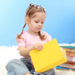 Cute little girl with colorful books, on blue background — Stock Photo