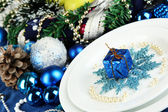 Small Christmas gift on plate on serving Christmas table in blue tone close-up — Stock Photo