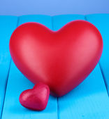 Decorative red hearts on blue wooden table on blue background — Stock Photo