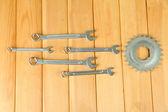 Metal zahnrad und schraubenschlüssel auf hölzernen hintergrund — Stockfoto