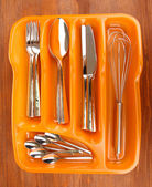 Orange plastic cutlery tray with checked cutlery on wooden table — Stock Photo