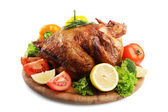 Whole roasted chicken on wooden plate with vegetables, isolated on white — Stock Photo
