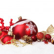 Beautiful red Christmas balls and cones on snow isolated on white — Stock Photo #19275251