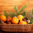 Christmas composition in basket with oranges and fir tree, on wooden background — Stock Photo