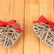 Wicker hearts with red bow on wooden background — Stock Photo