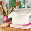 Chef's hat with battledore and cook book on board on wooden table on window background — Stock Photo