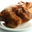 Foto Stock: Tasty whole roasted chicken on plate, isolated on white
