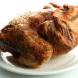 Tasty whole roasted chicken on plate, isolated on white — Stock Photo