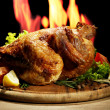 Whole roasted chicken with vegetables on plate, on flame background — Stock Photo