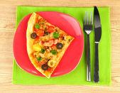 Placa con una rebanada de pizza deliciosa sobre fondo de madera — Foto de Stock