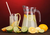 Citrus lemonade in pitcher and glass of citrus around on wooden table on red background — Stock Photo