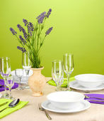 Table setting in violet and green tones on color background — Stock Photo