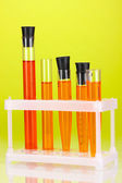 Test-tubes with a colorful solution on green background close-up — Photo