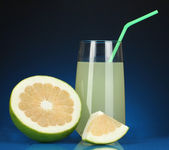 Delicious sweetie juice in glass and sweetie next to it on dark blue background — Stock Photo