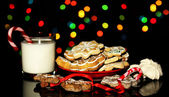 Christmas treats with glass of milk on Christmas lights background — Stock Photo