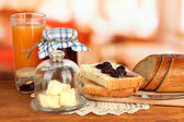 Butter on glass saucer with glass cover and fresh bread, jam on bright background — Stock Photo