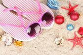 Christmas balls,seashells andh beach accessories on sand, close-up — Stock Photo