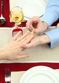A man proposing and holding up an engagement ring over restaurant table — Stock Photo
