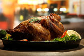 Whole roasted chicken with vegetables on plate, on wooden table in cafe — Stock Photo