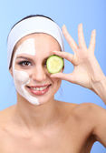 Young woman with clay facial mask, on blue background — Stock Photo