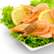 Boiled shrimps with lemon and lettuce leaves on plate, isolated on white — Stock Photo