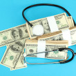 Healthcare cost concept: stethoscope and dollars on blue background — Stock Photo #19306833