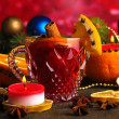 Fragrant mulled wine in glass with spices and oranges around on wooden table on red background — Lizenzfreies Foto