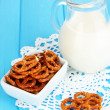 Tasty pretzels in white bowl and milk jug on wooden table close-up — Stock Photo #19307023