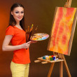 Beautiful young woman painter at work, on bright color background — Stock Photo