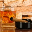 Glass of whiskey and cigar on brick wall background — Stock Photo