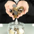 Stock Photo: Saving, female hands putting coins into glass bottle, isolated on white