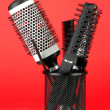 Iron basket with combs and round hair brushes, on color background — Stockfoto