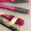 Comb brushes with hair, on grey background — Stock Photo