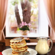 Sweet pancakes on plate with condensed milk on table in room — Stock Photo #19308477