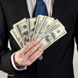 Business man holds lot of money on grey background — Stock Photo #19308523