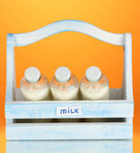 Milk in bottles in wooden box on orange background — Stock Photo