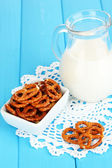 Tasty pretzels in white bowl and milk jug on wooden table close-up — Stock Photo