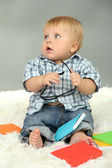 Little boy with multicolor books, on white carpet — Stock Photo