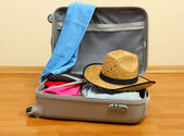Open silver suitcase with clothing in room — Stock Photo