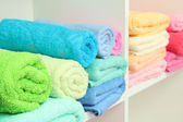 Colorful towels on shelves in bathroom — Stock Photo